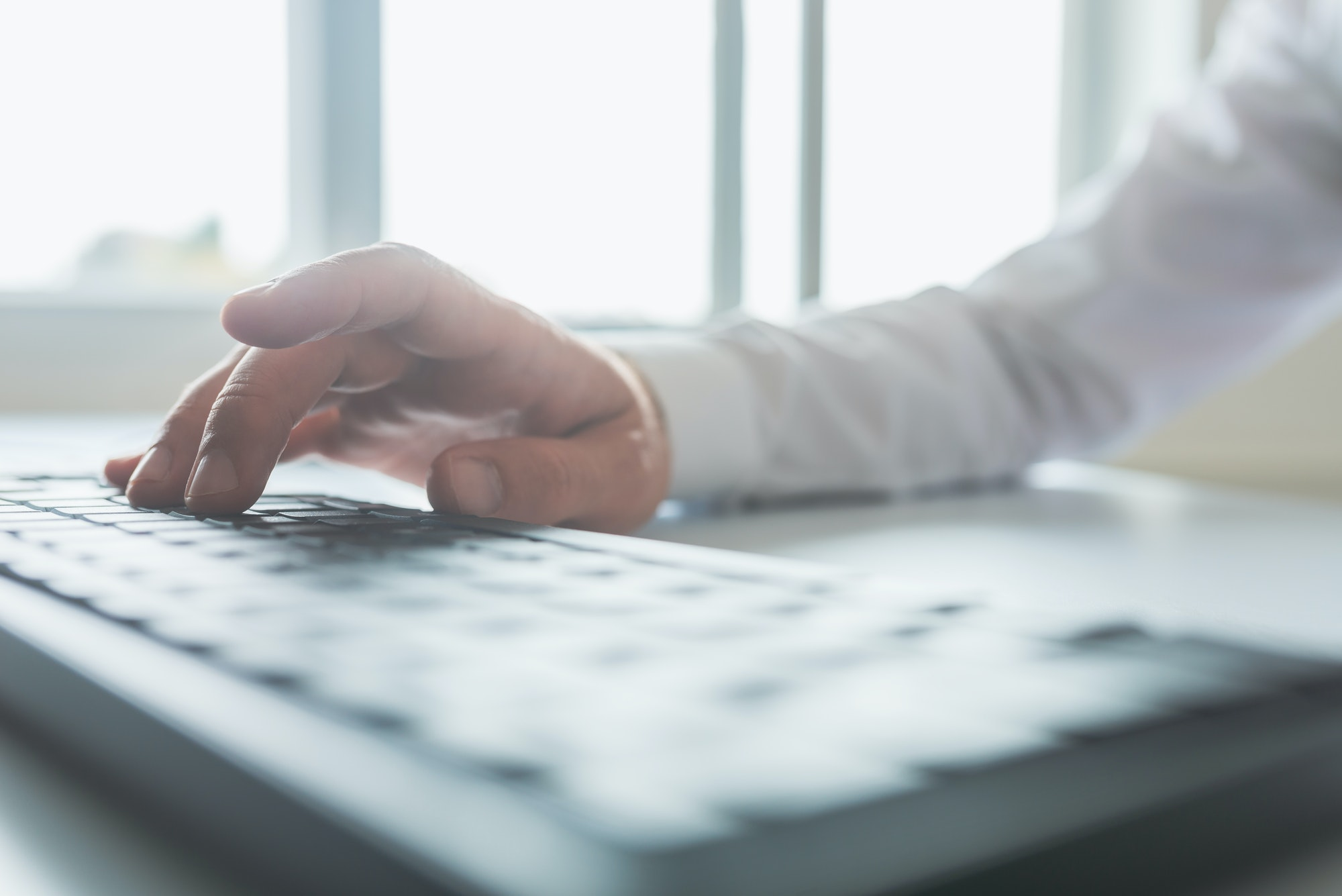 Bright image of a businessman typing on computer keyboard